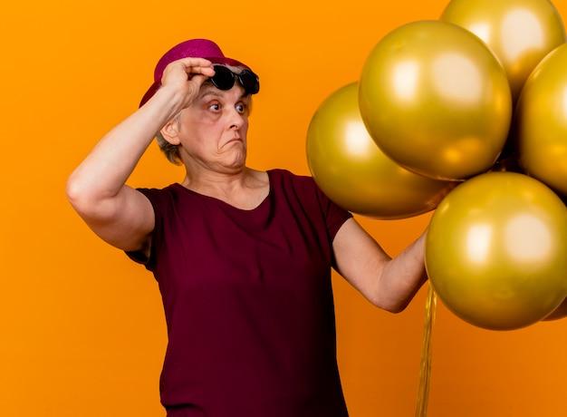 Surpris femme âgée portant chapeau de fête tient des lunettes de soleil debout et regardant des ballons d'hélium isolés sur un mur orange avec espace copie