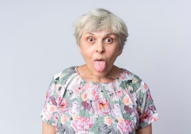 Surpris femme âgée sort la langue isolée sur un mur blanc