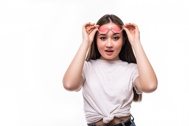 Surpris femme asiatique à lunettes de soleil isolé sur mur blanc