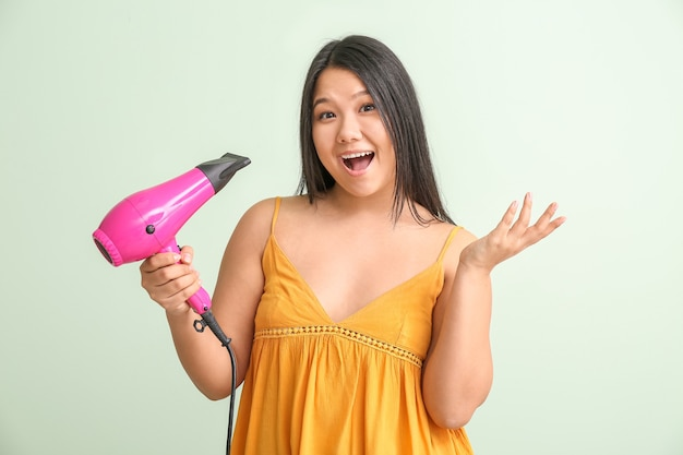 Surpris femme asiatique avec sèche-cheveux sur la couleur