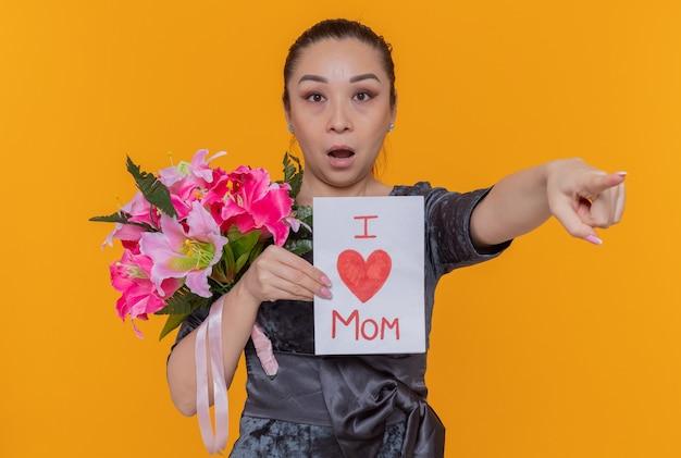 Surpris femme asiatique tenant une carte de voeux célébrant la journée internationale de la femme debout sur un mur orange