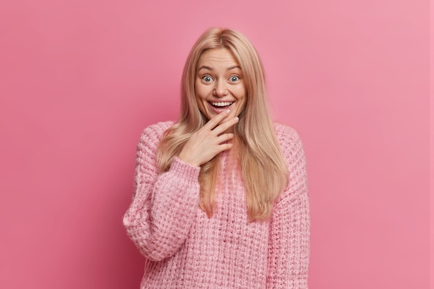 Surpris femme blonde amusée regarde quelque chose de merveilleux avec un large sourire perd le discours d'étonnement vêtu d'un pull d'hiver chaud