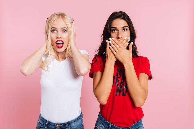 Surpris femme blonde couvrant ses oreilles et femme brune couvrant sa bouche sur rose
