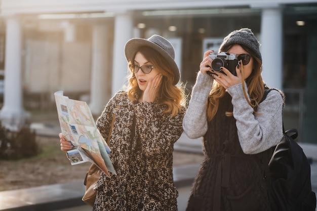 Surpris femme bouclée dans des verres en regardant la carte, touchant le visage pendant que son amie fait une photo de sites. jolie voyageuse marchant avec caméra et sa sœur à la recherche de lieux intéressants.