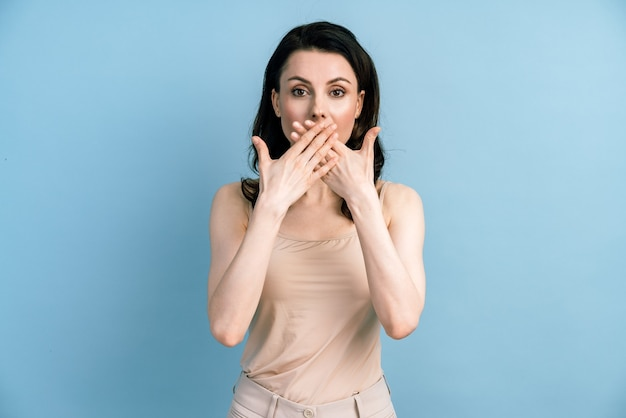 Surpris femme brune inquiète en t-shirt fermant la bouche et regardant la caméra.