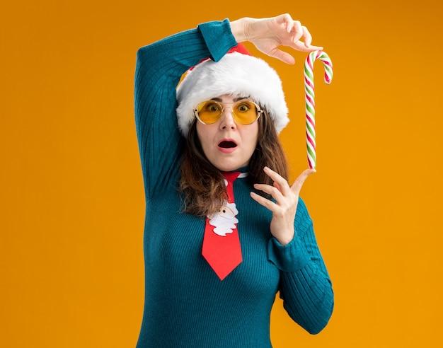 Surpris femme caucasienne adulte dans des lunettes de soleil avec bonnet de noel et cravate de père noël tenant la canne en bonbon avec les doigts isolés sur fond orange avec espace copie