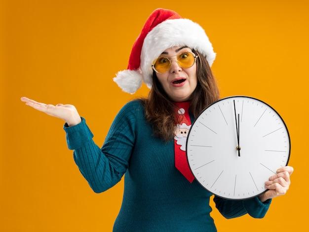 Surpris femme caucasienne adulte dans des lunettes de soleil avec bonnet de noel et cravate de père noël tenant horloge et gardant la main ouverte isolé sur fond orange avec espace copie