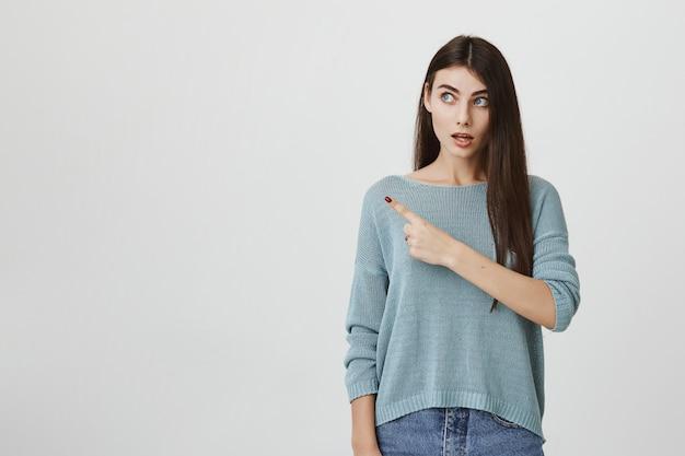 Surpris femme haletante regardant et pointant vers la gauche à la bannière