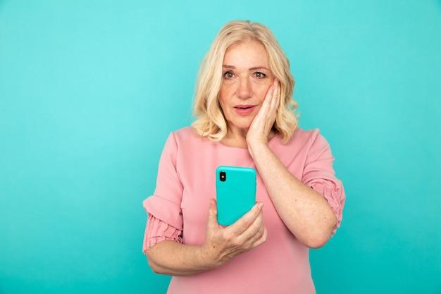 Surpris femme mature regardant le téléphone.