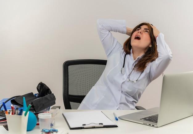 Surpris femme médecin d'âge moyen portant portant une robe médicale avec stéthoscope assis au bureau de travail sur un ordinateur portable avec des outils médicaux à la recherche et a saisi la tête sur le mur blanc