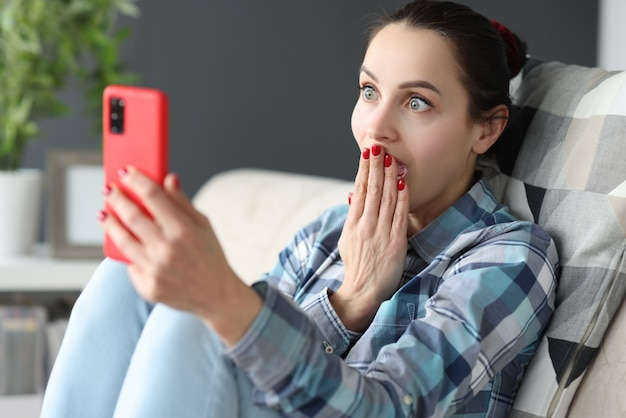 Surpris femme regarde l'écran du smartphone alors qu'il était assis sur le canapé