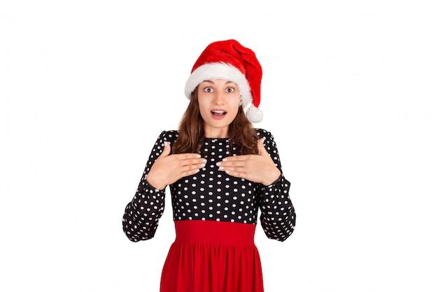 Surpris femme en robe tenant les mains sur la poitrine souriant étant touché et heureux. fille émotive au chapeau de noël père noël isolé