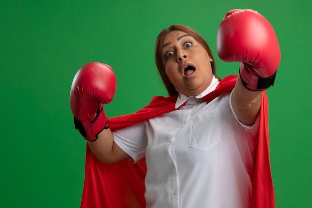 Surpris femme de super-héros d'âge moyen portant des gants de boxe tenant les mains isolées sur le vert