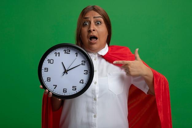 Surpris femme de super-héros d'âge moyen tenant et points à l'horloge murale isolé sur vert