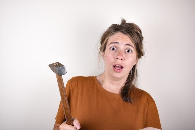 Surpris femme tenant un marteau dans ses mains