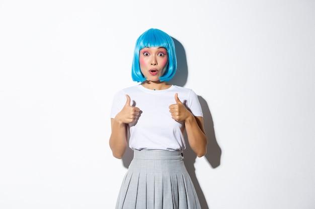 Surpris fille asiatique en perruque bleue haletant étonné, montrant le pouce en l'air d'approbation, debout.