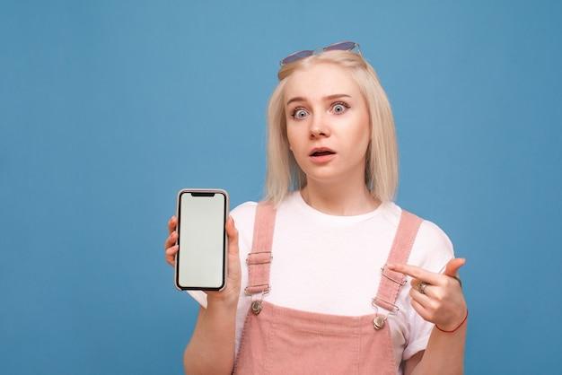 Surpris fille porte un léger vêtement décontracté, est titulaire d'un smartphone avec un écran blanc