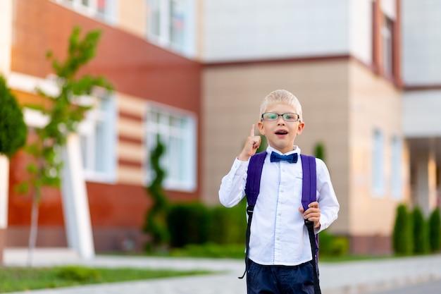 Surpris garçon blond écolier dans des verres avec un sac à dos se tient à l'école et montre un coup de pouce