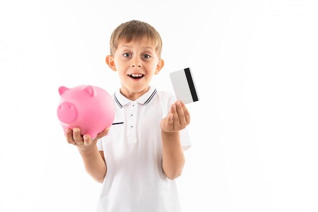 Surpris garçon caucasien avec tirelire et carte de crédit avec maquette sur blanc