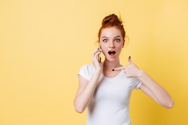 Surpris gingembre femme en t-shirt parler et pointant sur smartphone