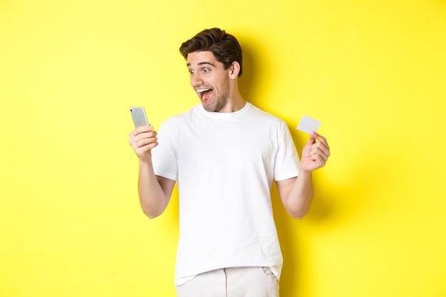 Surpris guy holding smartphone et carte de crédit, achats en ligne le vendredi noir, debout sur un mur jaune