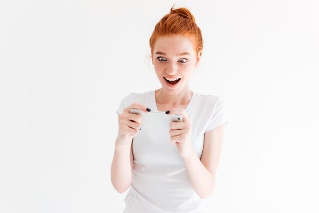 Surpris heureuse femme au gingembre en t-shirt jouant sur son smartphone
