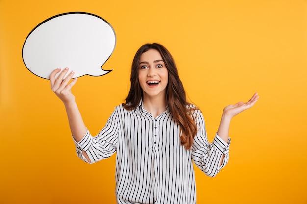 Surpris heureuse femme brune en chemise tenant une bulle de dialogue vide
