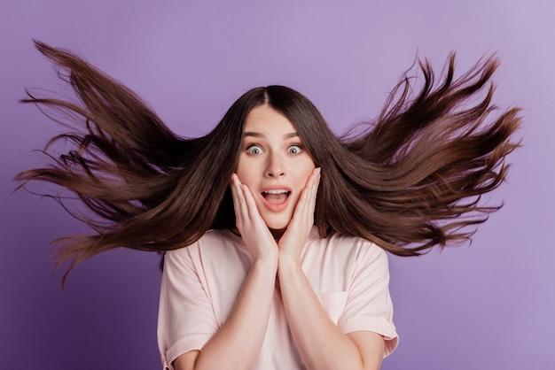 Surpris heureux belle femme coup de vent coiffure bouche ouverte sur fond violet