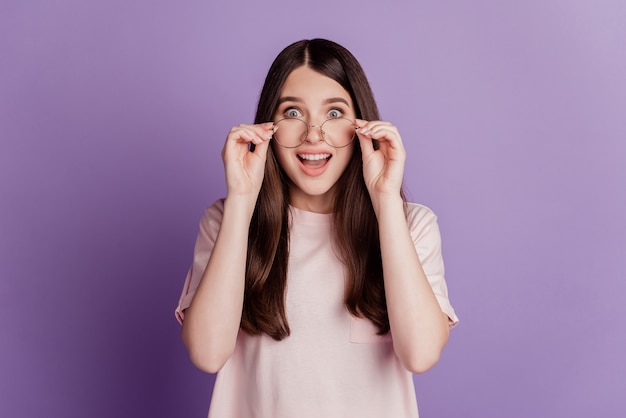 Surpris heureux belle femme dans des verres bouche ouverte sur mur violet