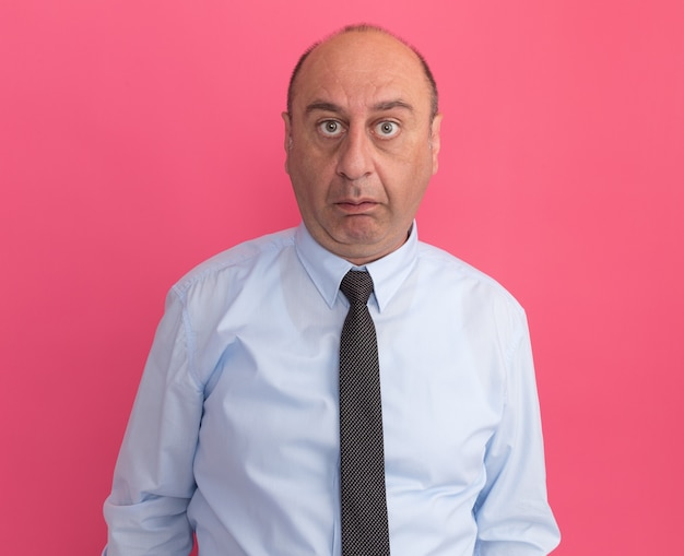 Surpris homme d'âge moyen portant un t-shirt blanc avec cravate isolé sur mur rose