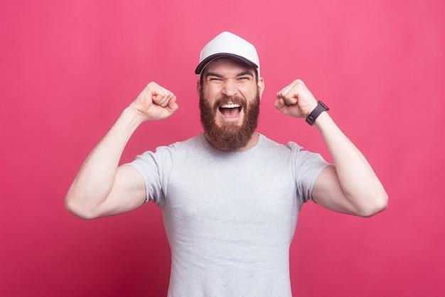 Surpris l'homme barbu célèbre le succès sur le mur rose
