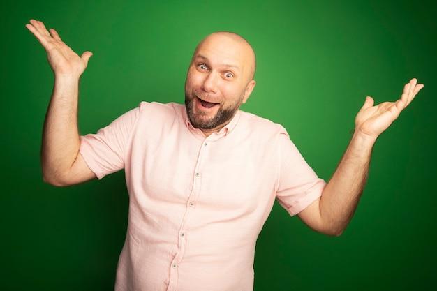 Surpris homme chauve d'âge moyen portant un t-shirt rose répandant les mains isolées sur le vert