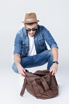 Surpris homme dans un chapeau regarde dans un sac en cuir vide l'argent a disparu