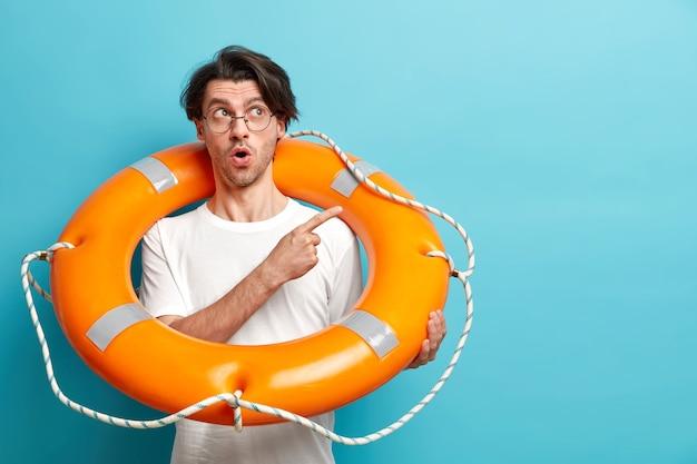 Surpris homme européen prêt à aller dans un endroit ensoleillé pendant les vacances d'été porte une bouée de sauvetage gonflée pointe à un espace vide