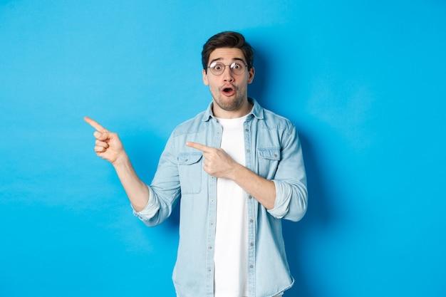 Surpris homme à lunettes pointant du doigt à gauche, posant une question sur le produit, à l'intrigué, debout sur un mur bleu