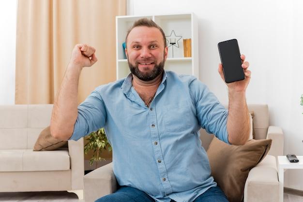 Surpris homme slave adulte est assis sur un fauteuil en gardant le poing en l'air tenant le téléphone à l'intérieur du salon