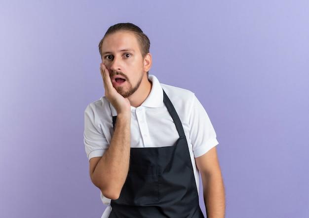 Surpris jeune beau coiffeur en uniforme mettant la main sur la joue isolé sur mur violet
