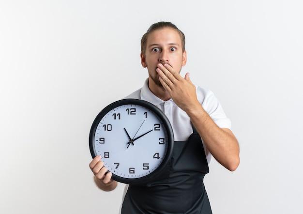 Surpris jeune beau coiffeur en uniforme tenant horloge et mettant la main sur la bouche isolé sur mur blanc