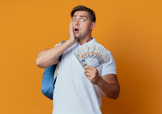 Surpris jeune beau étudiant masculin portant un sac à dos tenant de l'argent et mettant la main
