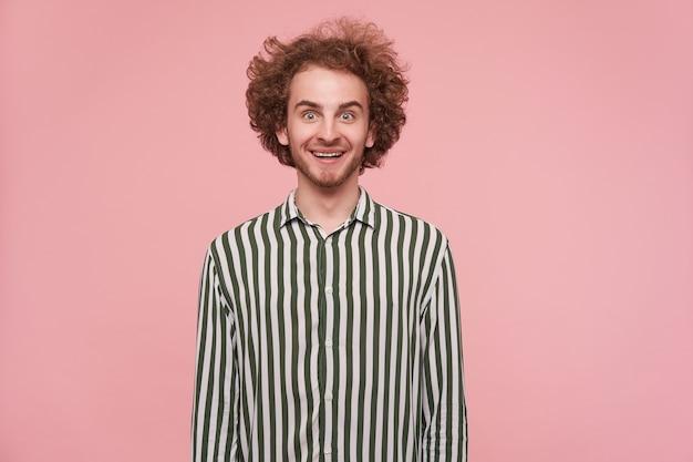 Surpris jeune beau mâle rousse avec barbe autour de ses yeux verts tout en regardant avec étonnement la caméra et souriant joyeusement, isolé sur un mur rose en tenue décontractée
