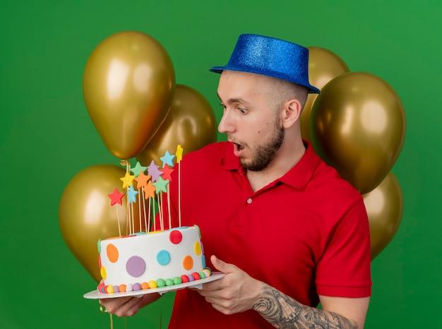 Surpris jeune beau mec de fête slave portant chapeau de fête debout devant des ballons tenant et regardant le gâteau d'anniversaire isolé sur fond vert