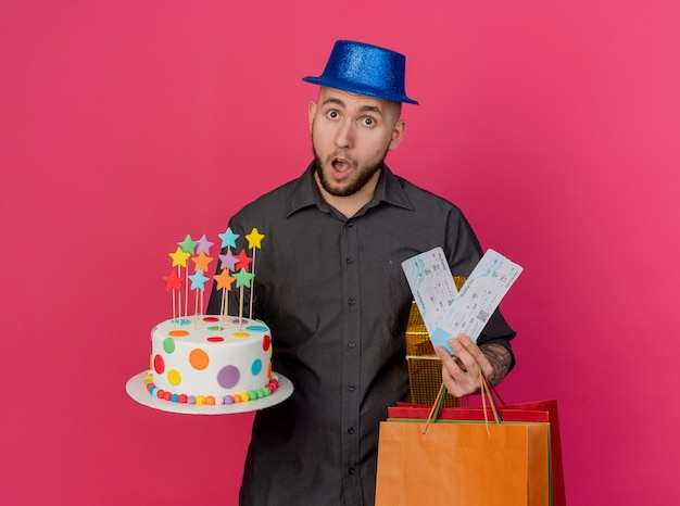 Surpris jeune beau mec de fête slave portant un chapeau de fête tenant un paquet de cadeau d'argent de gâteau d'anniversaire et des sacs en papier regardant la caméra isolée sur fond cramoisi