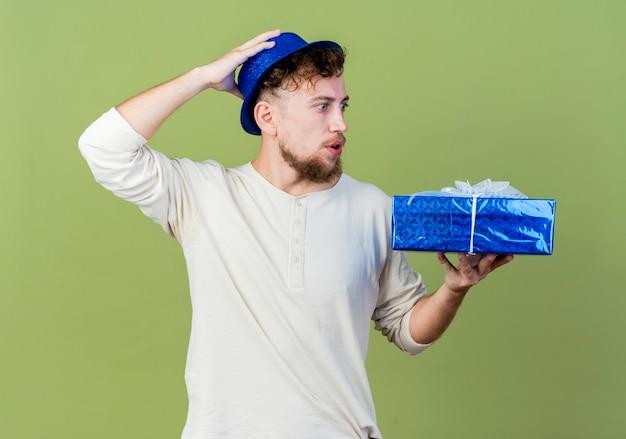 Surpris jeune beau mec de parti slave portant chapeau de fête tenant et regardant la boîte-cadeau en gardant la main sur la tête isolé sur fond vert olive