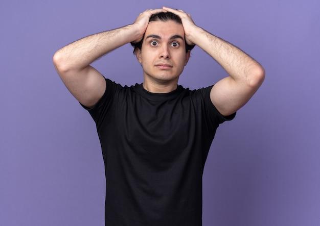Surpris, un jeune beau mec portant un t-shirt noir a attrapé la tête isolée sur un mur violet