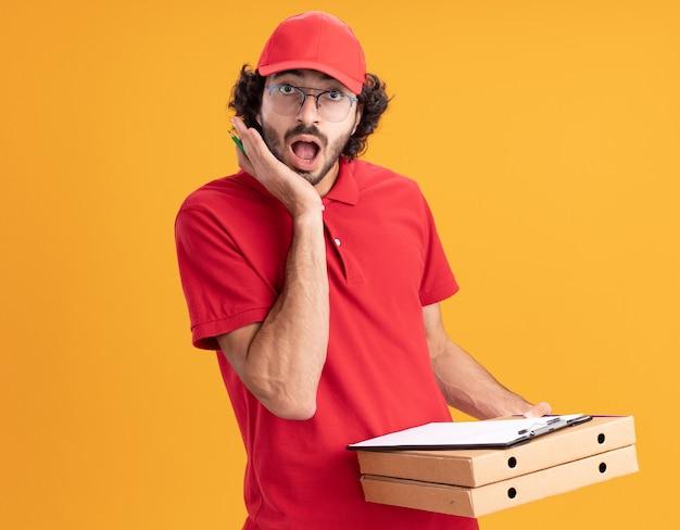 Surpris, jeune, caucasien, livreur, dans, uniforme rouge, et, casquette, porter, lunettes, tenue, pizza, paquets, presse-papiers, crayon, regarder, devant, garder, main, figure