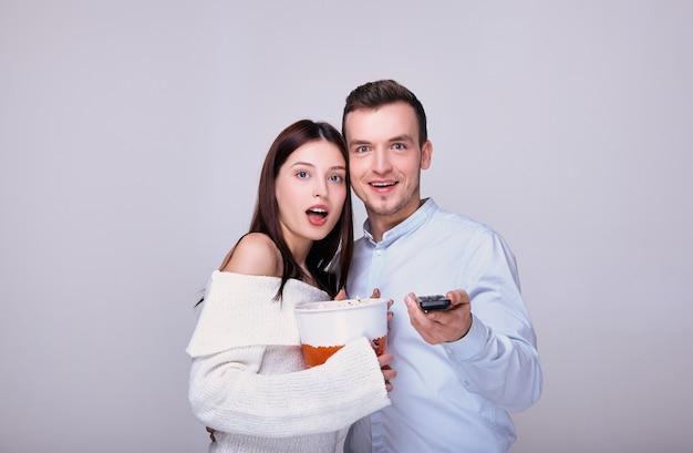 Surpris de jeune couple avec du pop-corn et une télécommande du téléviseur.
