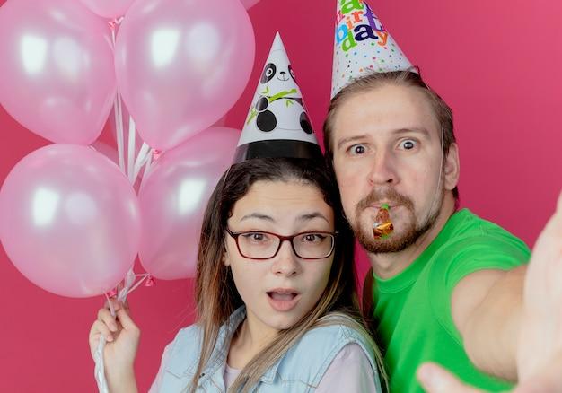 Surpris jeune couple portant chapeau de fête regarde fille tenant des ballons d'hélium et homme soufflant sifflet isolé sur mur rose