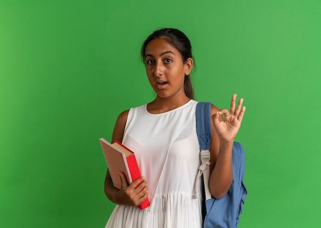Surpris jeune écolière portant un sac à dos tenant un livre avec un cahier et montrant un geste okey sur vert