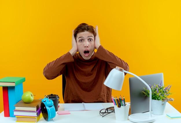 Surpris jeune étudiant garçon assis au bureau avec des outils scolaires couverts oreilles avec main sur jaune