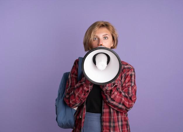 Surpris, une jeune étudiante slave portant un sac à dos parle dans un haut-parleur